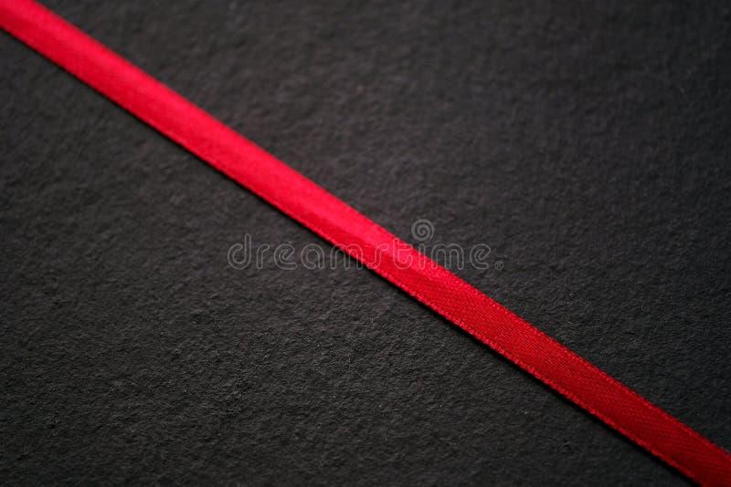 Красная лента на черноте, текстуре стоковое изображение