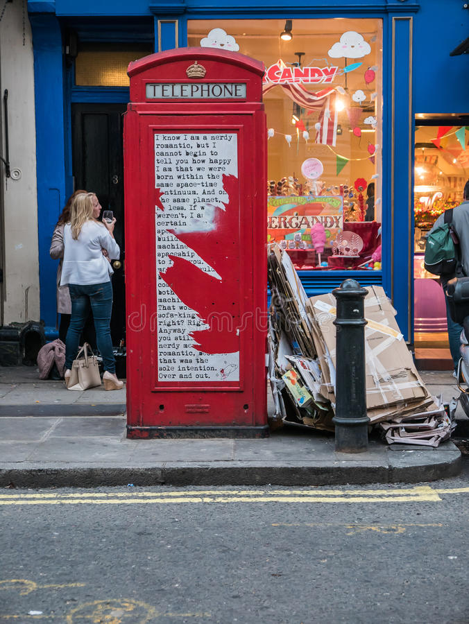 Красная переговорная будка Лондона с поэзией улицы стоковое фото