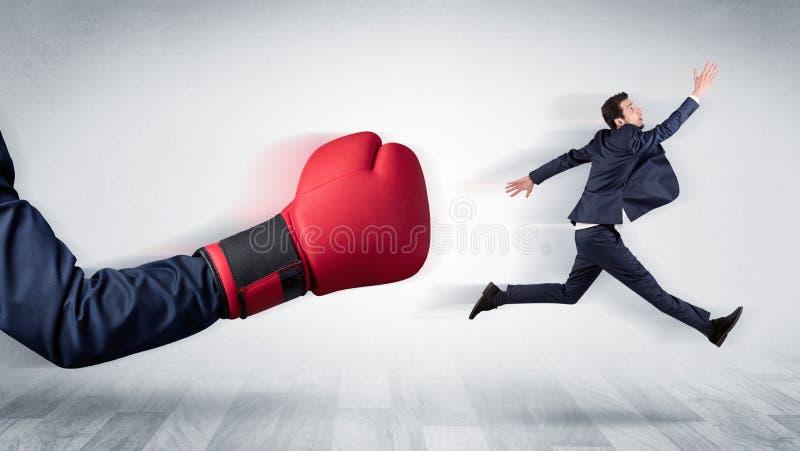 Красная перчатка бокса стучает вне маленьким бизнесменом стоковая фотография rf