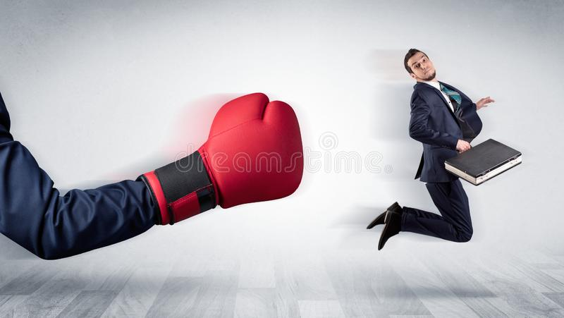 Красная перчатка бокса стучает вне маленьким бизнесменом стоковое фото rf