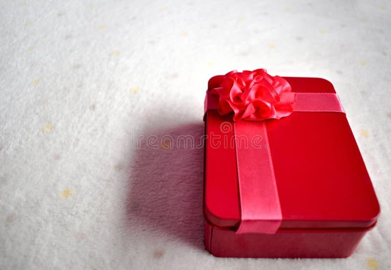Красная подарочная коробка на мягкой ткани стоковое фото