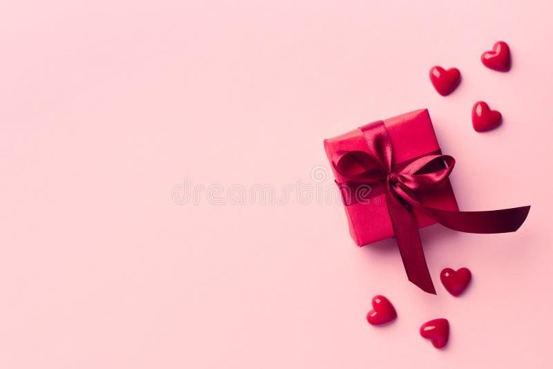 Красная подарочная коробка на розовой предпосылке стоковые изображения