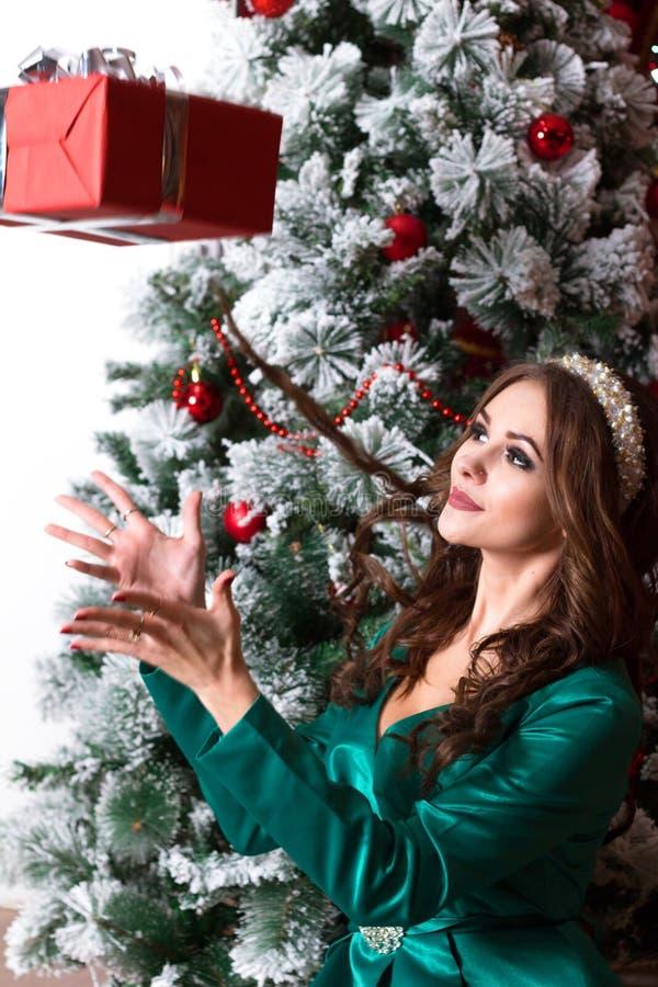 Красная подарочная коробка падает в руки красивой девушки в зеленом платье около украшенной рождественской елки Новый Год или рож стоковая фотография