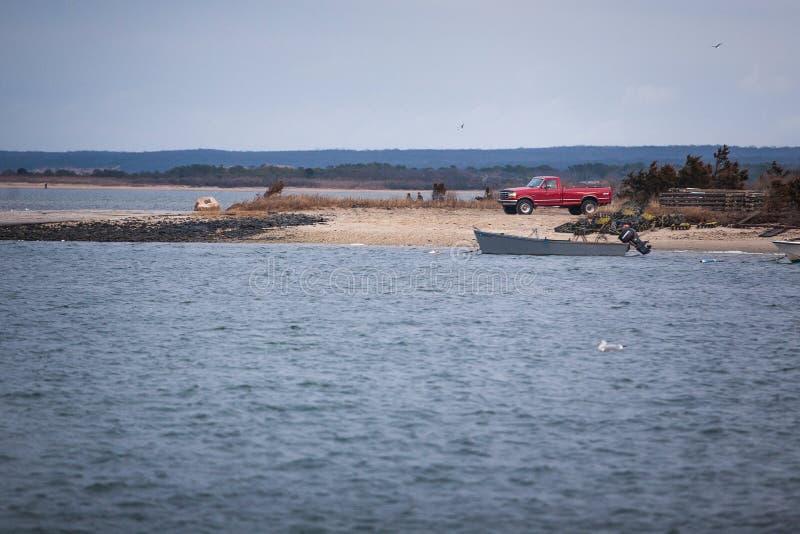 Красная приемистость на побережье с шлюпкой стоковые фотографии rf