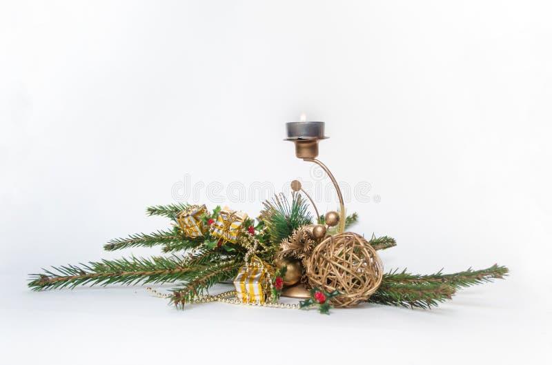 Красная свеча рождества, украшенная с ветвями ели, на белой предпосылке стоковые изображения