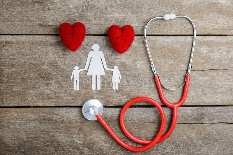 Красная семья сердца, стетоскопа и бумаги цепная на деревянном столе стоковое изображение rf
