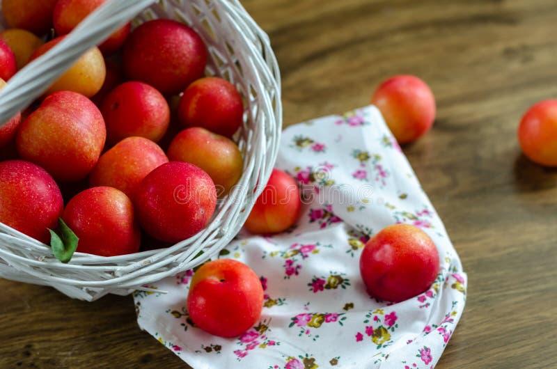 Красная слива в плетеной корзине на деревянном столе стоковые фотографии rf
