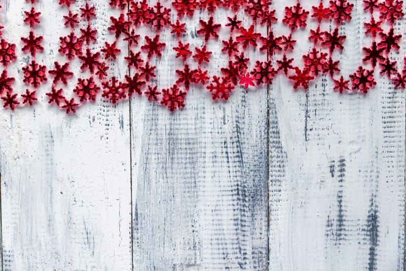 Красная снежинка отбортовывает гирлянду на белой предпосылке стоковые изображения rf