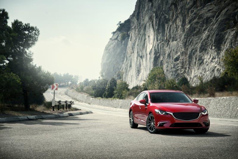 Красная стойка автомобиля на дороге около гор на дневном времени стоковое изображение rf