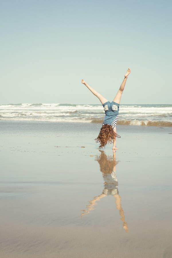 Красная с волосами девушка делая стойку или колесо телеги руки на пляже прибоя Новой Зеландии стоковая фотография rf