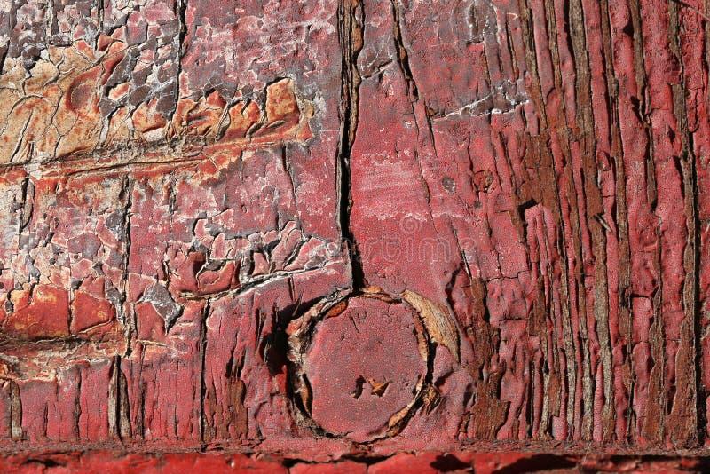 Красная треснутая краска на старой доске, шарнир двери в форме arr стоковые изображения