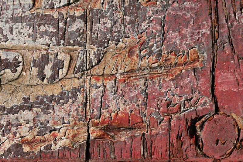 Красная треснутая краска на старой доске, шарнир двери в форме arr стоковое фото rf