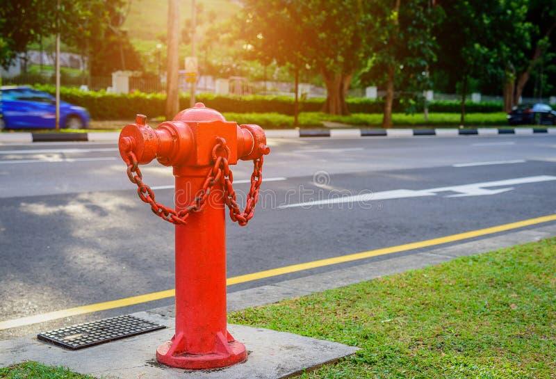 Красная труба водопровода жидкостного огнетушителя около дороги стоковая фотография