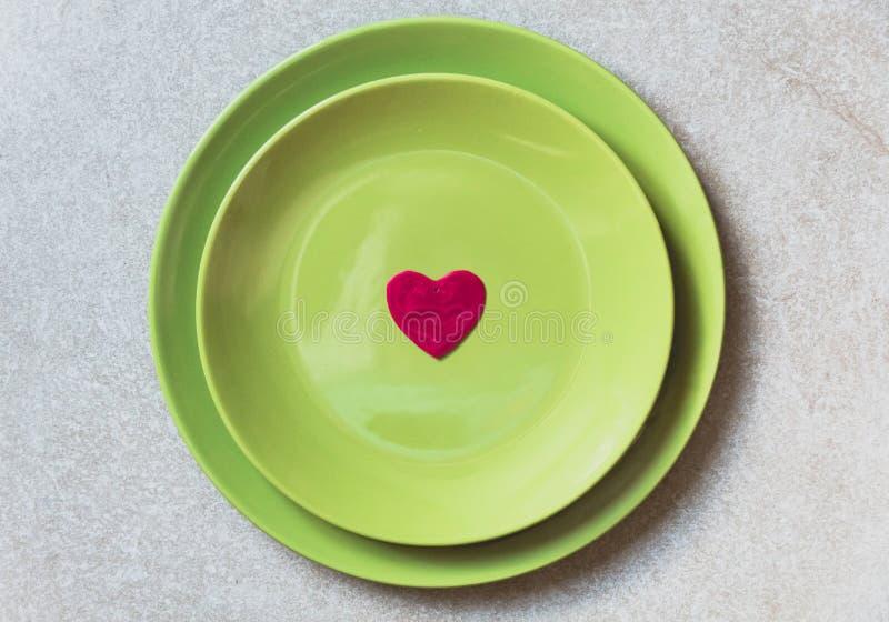 Красная форма сердца в центре зеленых плит на серой предпосылке Плоское положение стоковые изображения