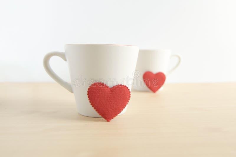 Красная форма сердца с 2 белыми кружками на деревянной таблице стоковое фото rf