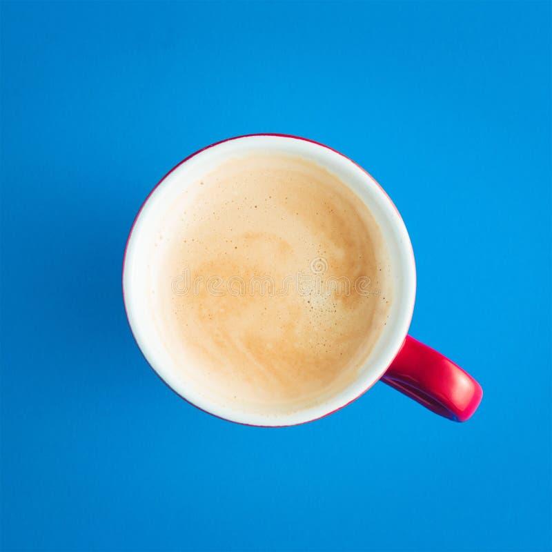 Красная чашка кофе с пеной на голубой предпосылке стоковое изображение
