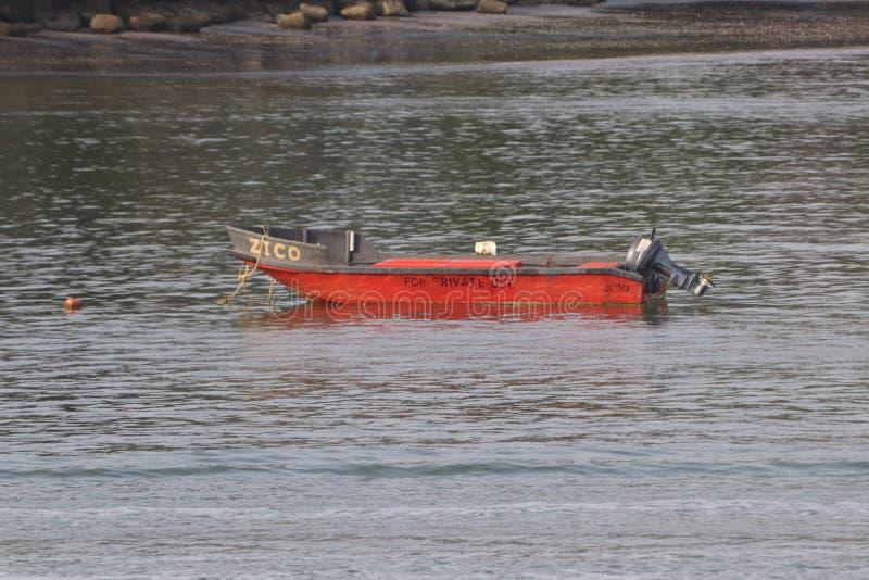 Красная шлюпка в море стоковое изображение rf