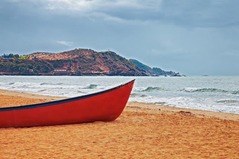Красная шлюпка на песчаном пляже стоковое фото rf