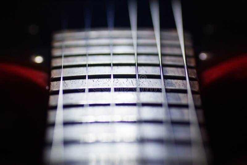 Красная электрическая гитара в макросе, строки закрывает вверх, деталь аппаратуры музыканта стоковые фотографии rf