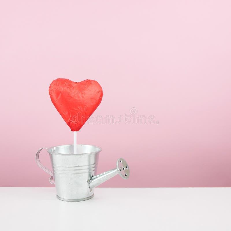 Красная foiled ручка сердца шоколада с малой моча чонсервной банкой стоковая фотография rf