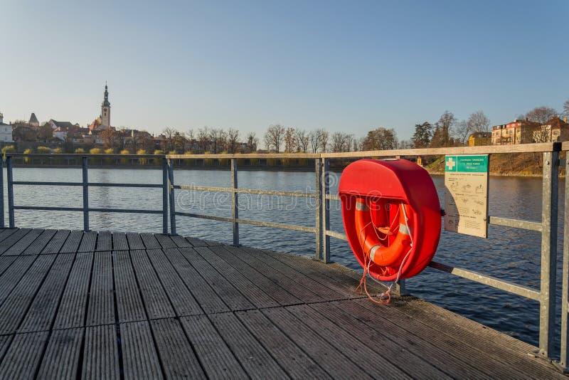 Красная lifebuoy смертная казнь через повешение на деревянной пристани, пруде Джордан, Таборе, самой старой запруде в чехии, солн стоковая фотография rf