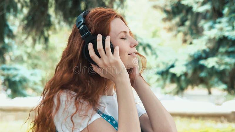 Красноголовая девушка танцует на размытом фоне стоковая фотография rf