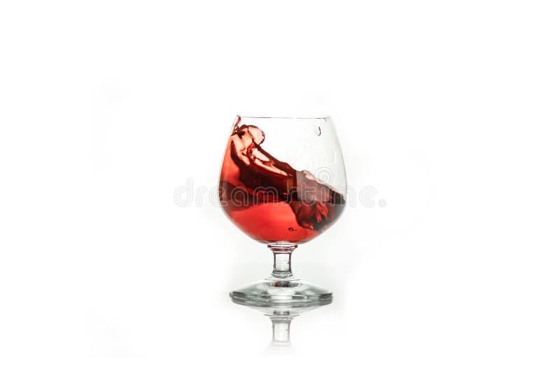Красное вино брызгая из стекла, на белом стоковое изображение