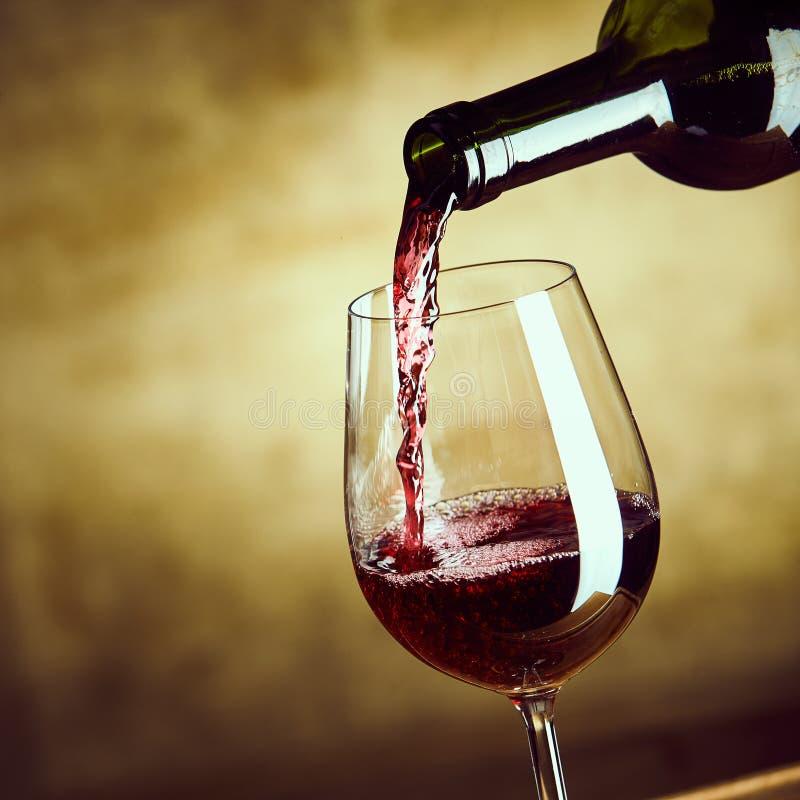 Красное вино будучи политым в рюмку стоковые фотографии rf