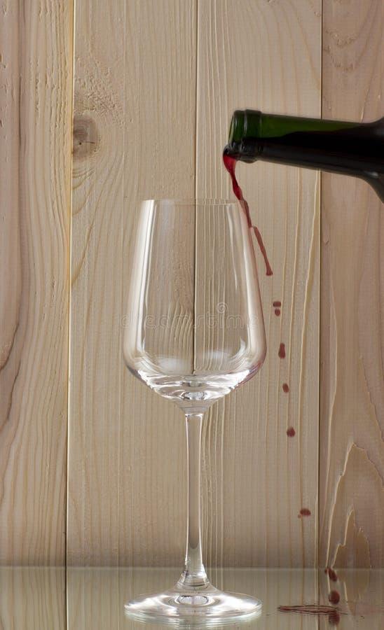 Красное вино будучи политым в стеклянную бутылку красного вина с гениальным стеклом на деревянной предпосылке на стеклянной стойк стоковые изображения rf