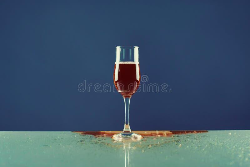 Красное вино в бокале на голубом фоне стоковые изображения