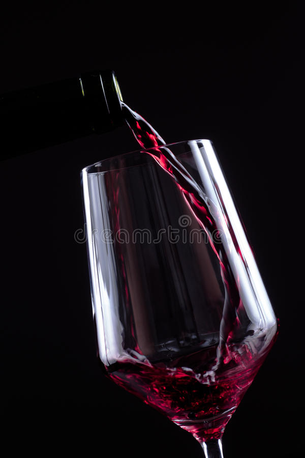Красное вино лить в рюмке от бутылки на черной предпосылке Меню дизайна винной карты с copyspace стоковые изображения rf