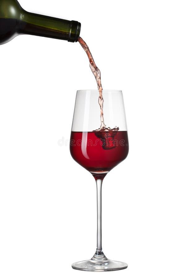 Красное вино лить в стекло при выплеск изолированный на белизне стоковые фотографии rf