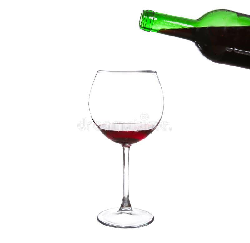Красное вино лить от бутылки в большое стекло стоковые изображения rf