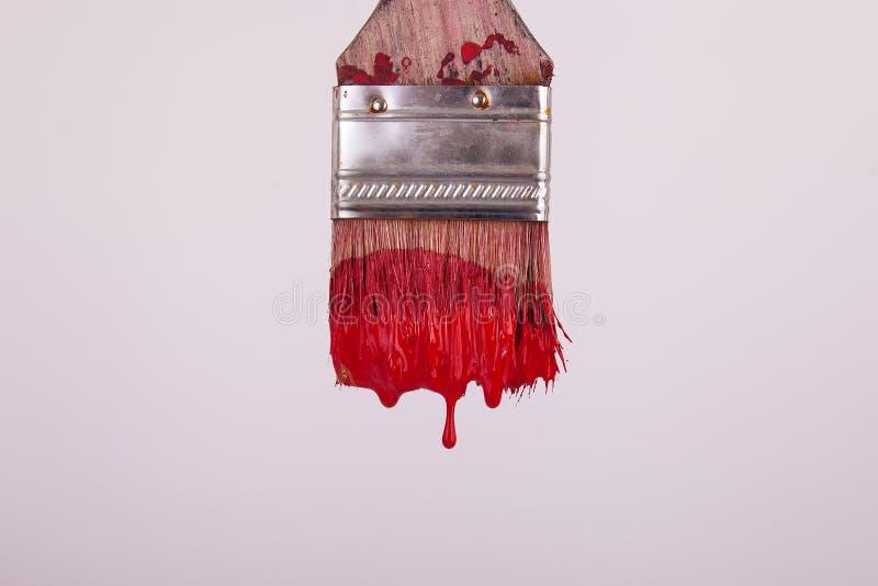 Красное влажное капание краски от paintbrush художников стоковая фотография rf