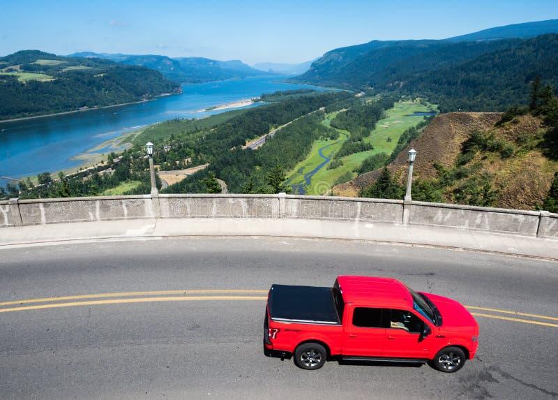 Красное вождение автомобиля вдоль сценарного маршрута около дома перспективы пункта кроны в ущелье Рекы Колумбия стоковые изображения