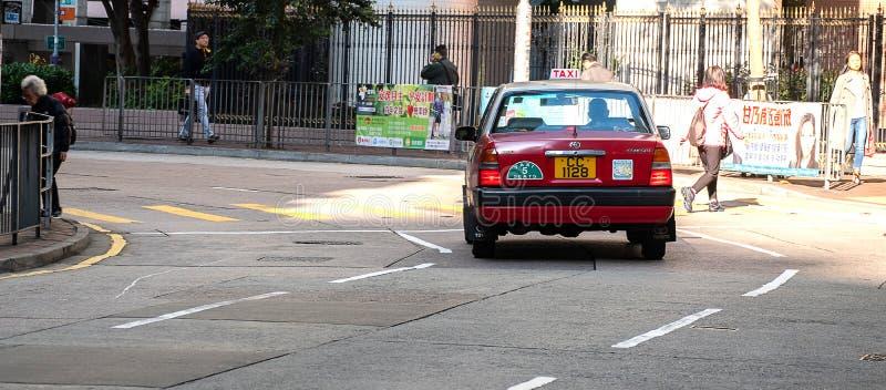 Красное и белое такси цветов, символ HK, на дороге Голливуд около района централи и Sheung болезненного; Гонконг, Китай, 16-ое де стоковое изображение rf