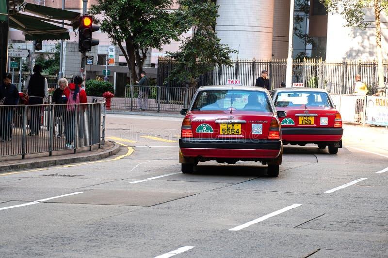Красное и белое такси цветов, символ HK, на дороге Голливуд около района централи и Sheung болезненного; Гонконг, Китай, 16-ое де стоковое фото