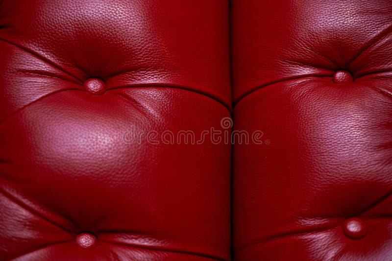 Красное кожаное драпирование софы, прокладки с кнопками E стоковая фотография