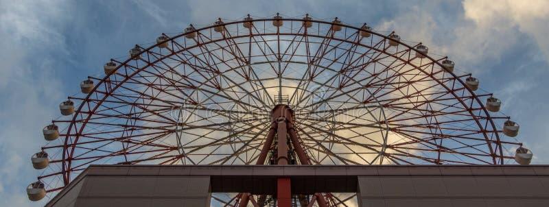 Красное колесо Ferris площади Amu на станции Кагошима Chuo МЛАДШЕГО против голубого неба Принятый от дна Размещенный в Кагошима,  стоковое изображение rf