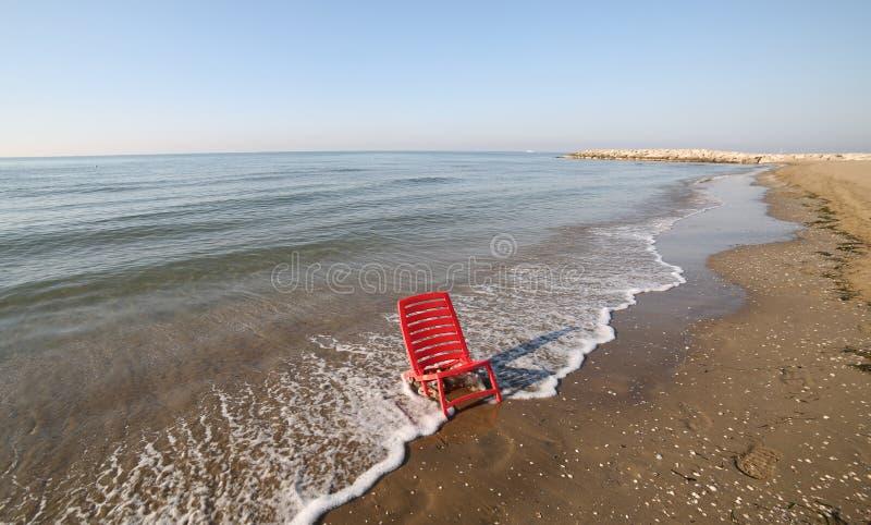 Красное малое deckchair, который будет ослаблять море в лете стоковое фото rf