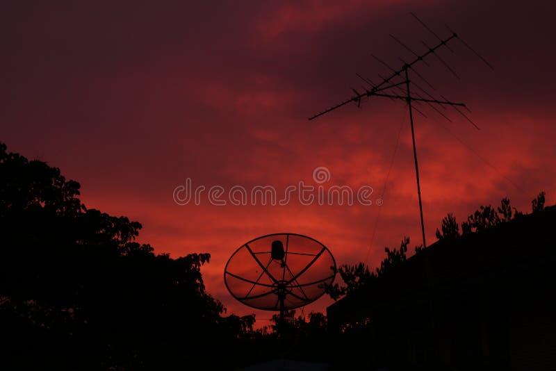 Красное небо вечером и спутник блюда стоковые изображения rf