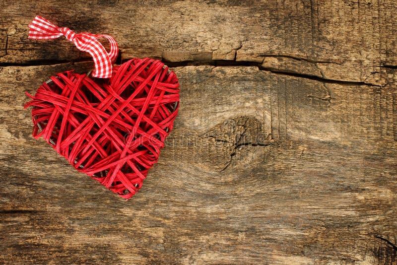 Красное плетеное сердце на деревянной предпосылке стоковое фото