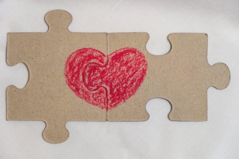Красное сердце нарисовано на кусках головоломки лежа рядом друг с другом стоковое изображение
