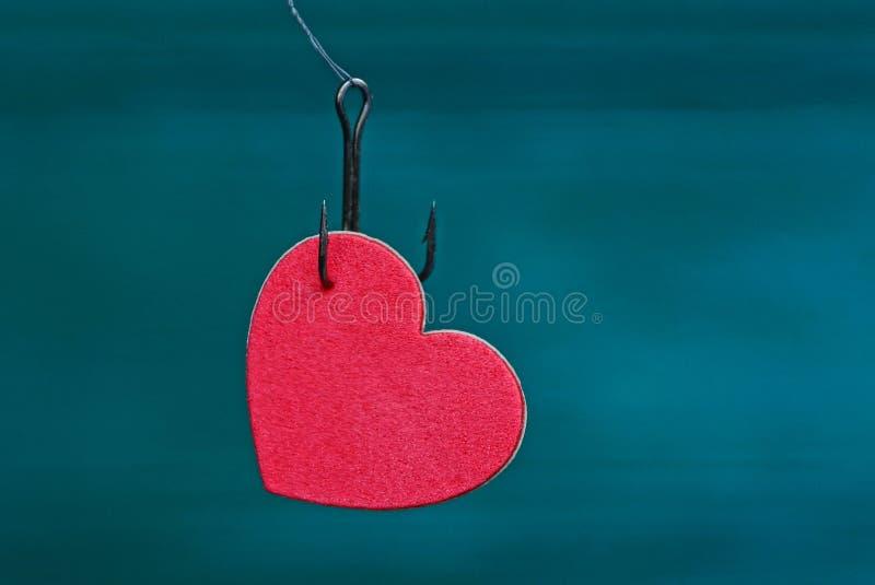Красное сердце на удя крюке на зеленой предпосылке стоковое изображение