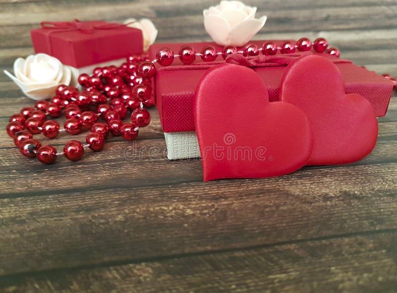Красное сердце, подарочная коробка отбортовывает деревянную предпосылку датировка декоративную стоковое изображение rf
