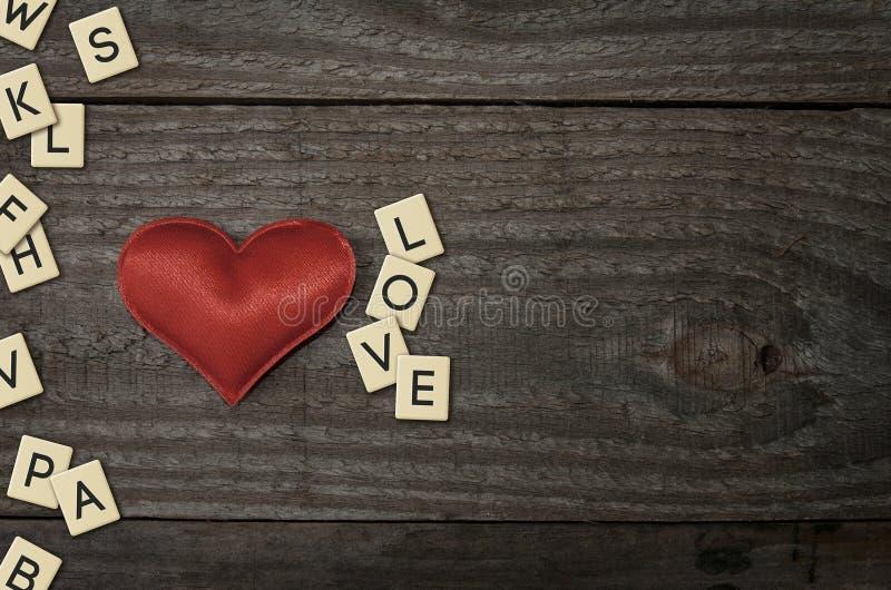 Красное сердце ткани на деревянном столе вместе с любовью слова стоковые фотографии rf