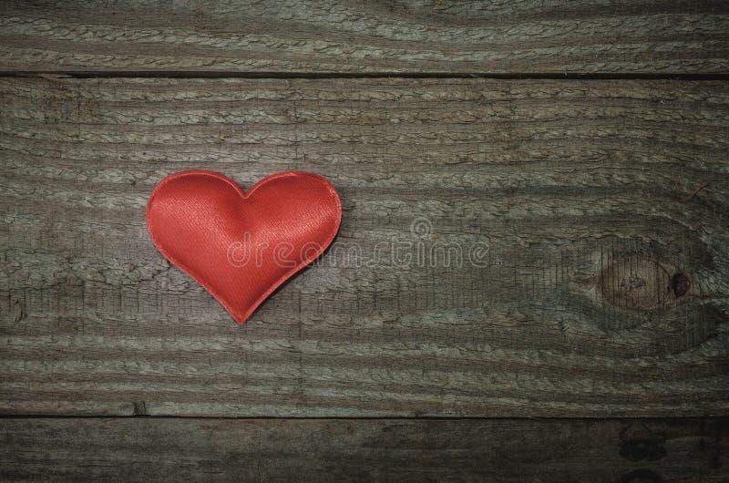 Красное сердце ткани на древесине стоковое изображение