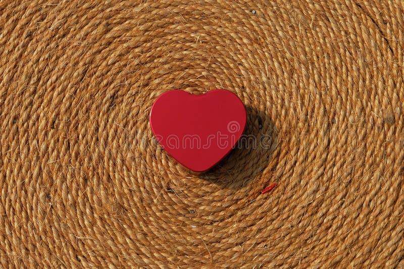 Красное сердце на спиральной текстуре веревочки стоковые фото