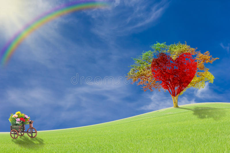 Красное сердце с большим деревом на луге стоковые изображения
