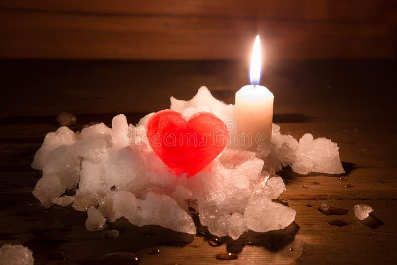 Красное сердце льда и горящая свеча на холме белого снега стоковые изображения